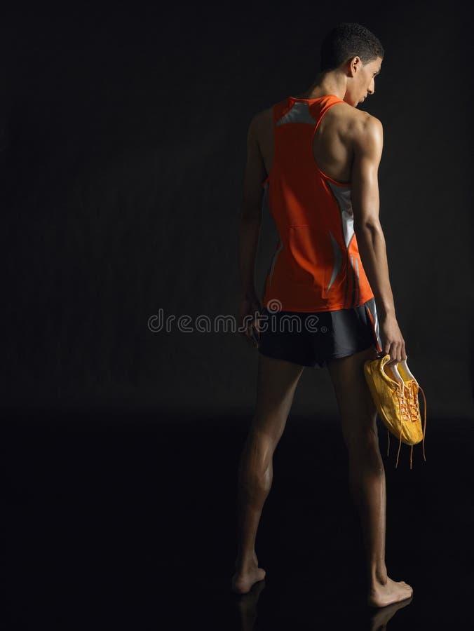 Во всю длину мужского спортсмена держа ботинки стоковая фотография rf