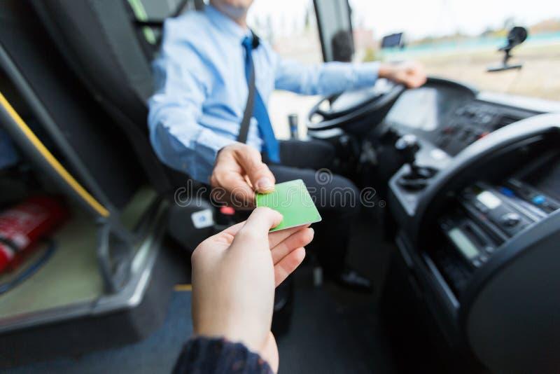 Водитель автобуса принимая билет или карточку от пассажира стоковая фотография