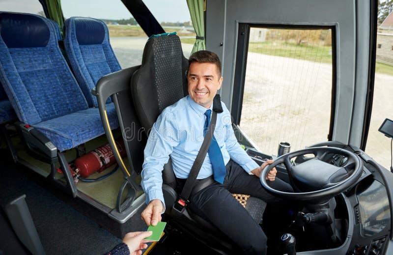 Водитель автобуса принимая билет или карточку от пассажира стоковое фото