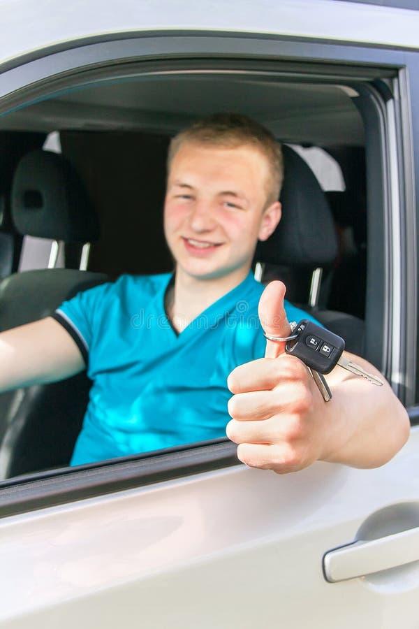 Водитель автомобиля Кавказский предназначенный для подростков мальчик показывая большие пальцы руки вверх, ключ автомобиля и ne стоковое изображение rf