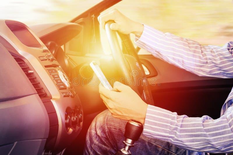 Водитель используя мобильный телефон: рука используя телефон посылая текст или положения находки и получает направления с картами стоковое фото