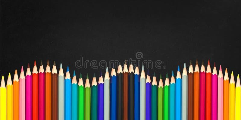 Волна красочных деревянных карандашей изолированных на черной предпосылке, назад к концепции школы стоковое изображение