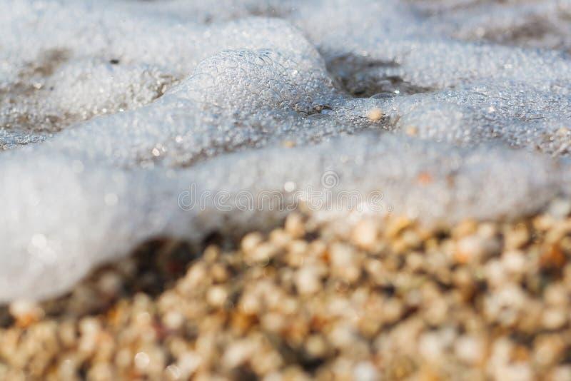 Волна моря свертывая над камешками стоковые изображения rf
