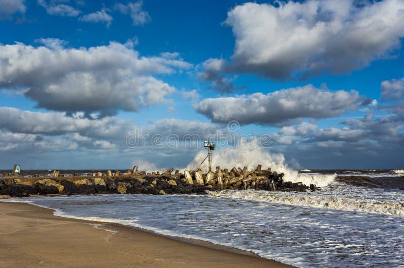 Волна разбивая на моле в океане стоковые фото