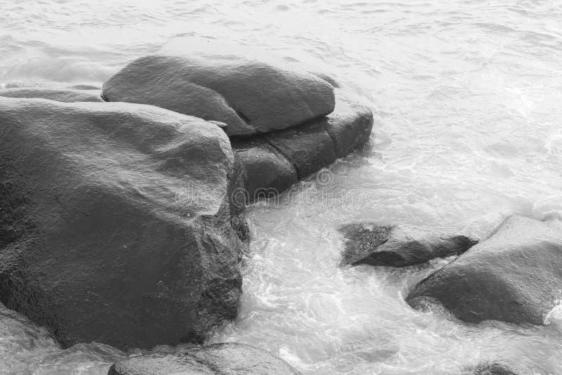 Волна разбивая на скалистом и пляже стоковые изображения
