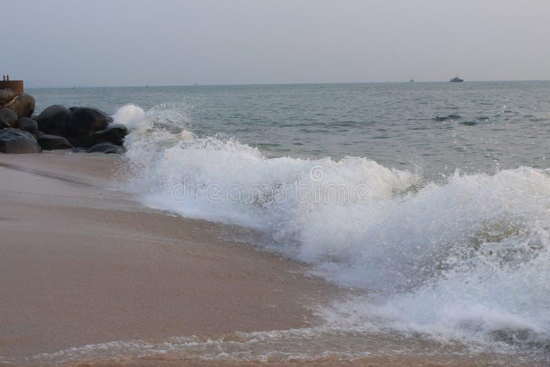 Волна разбивая на скалистом и пляже стоковое изображение