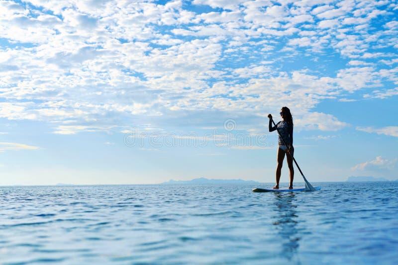 Водные виды спорта лета Силуэт женщины в море Здоровый уклад жизни стоковое фото rf