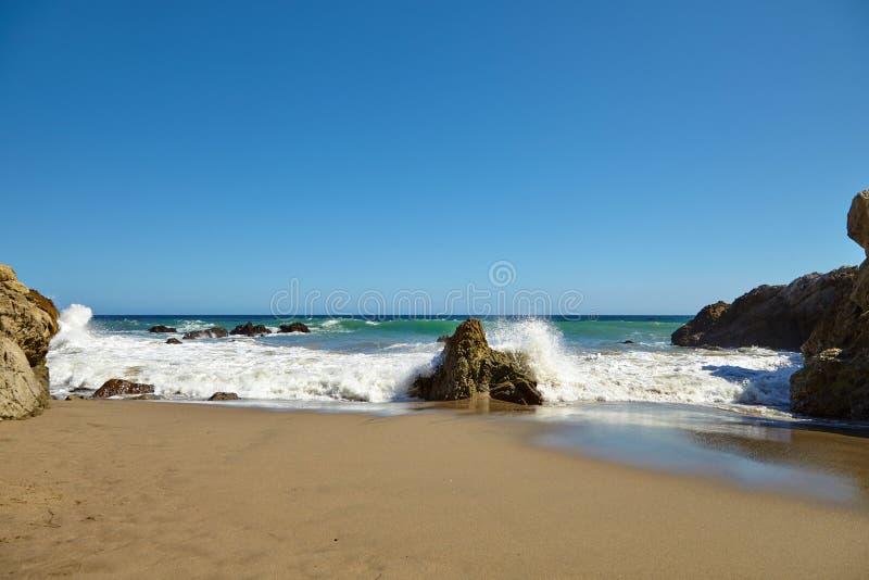 Волны бить против прибрежных утесов на скалах стоковые фотографии rf