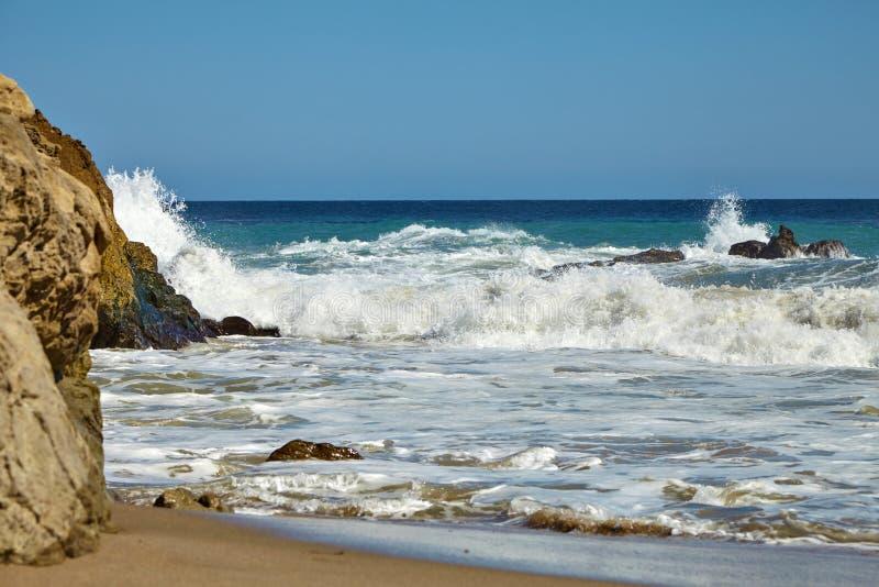 Волны бить против прибрежных утесов на скалах стоковые фото