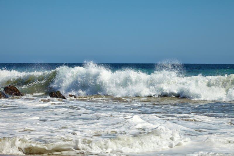Волны бить против прибрежных утесов на скалах стоковое изображение rf