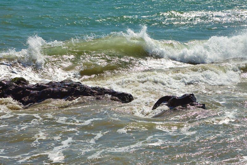 Волны бить против прибрежных утесов на скалах стоковые изображения