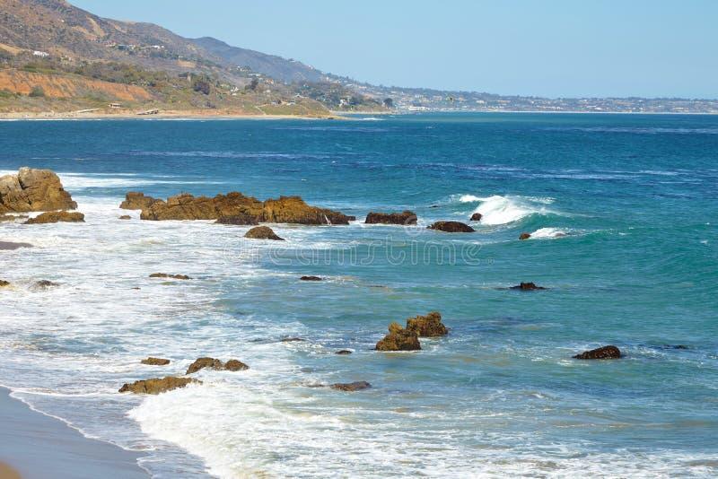 Волны бить против прибрежных утесов на скалах стоковое фото rf