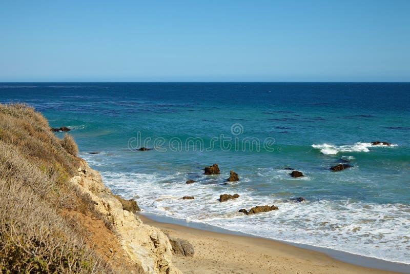 Волны бить против прибрежных утесов на скалах стоковая фотография