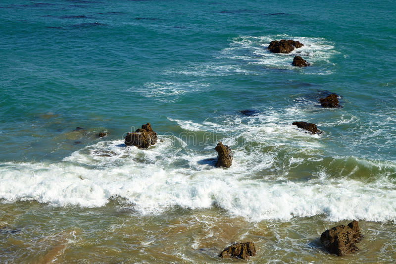 Волны бить против прибрежных утесов на скалах стоковая фотография rf