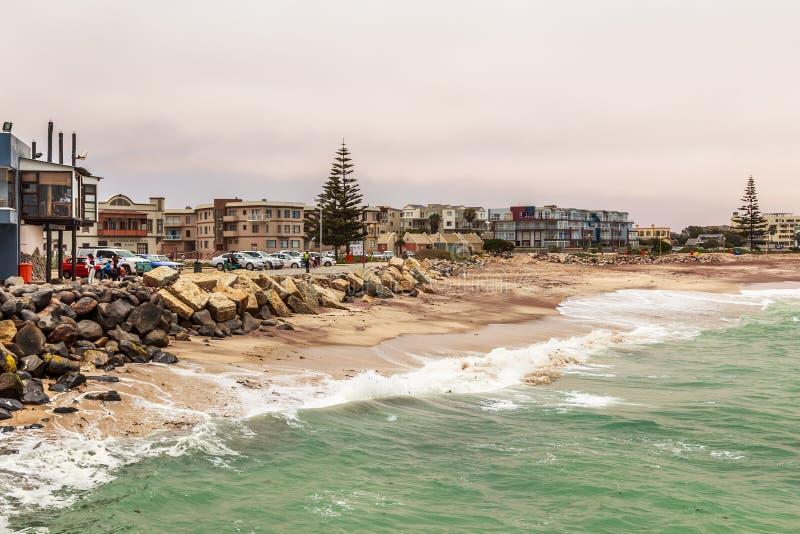 Волны, камни на береговой линии с домами в предпосылке, Swakop стоковое изображение