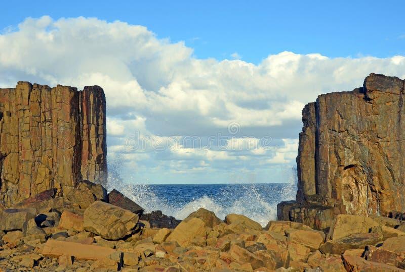 Волны ломая над и между образованиями базальта стоковые изображения