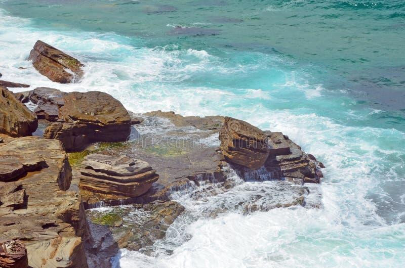Волны разбивая над скалистым берегом стоковые фото