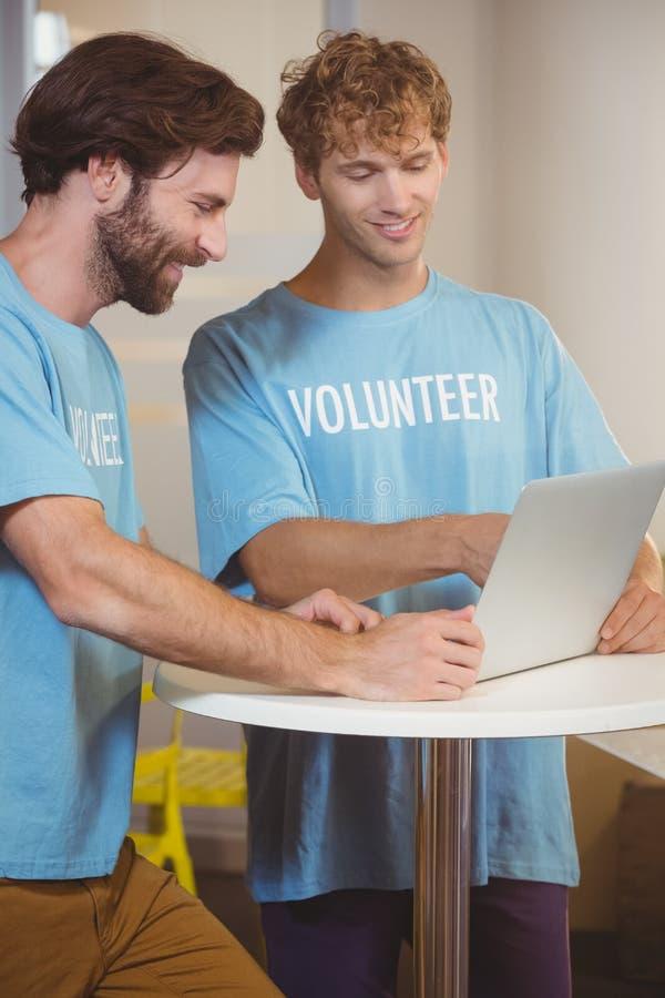 Волонтеры используя компьтер-книжку стоковые фотографии rf