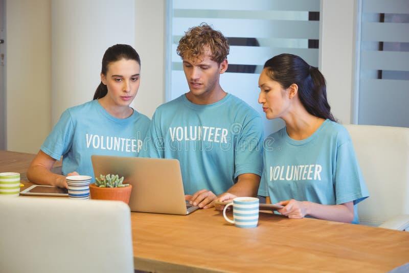 Волонтеры используя компьтер-книжку стоковая фотография
