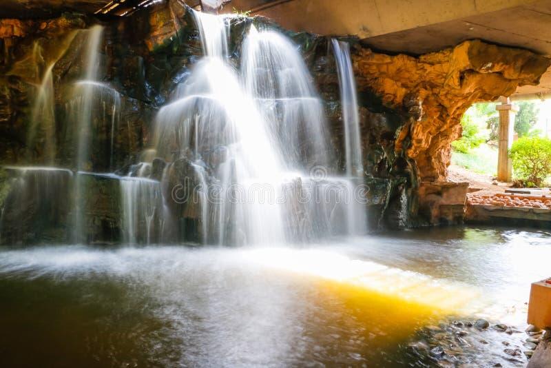 Водопад в парке в солнечном дне стоковые фотографии rf