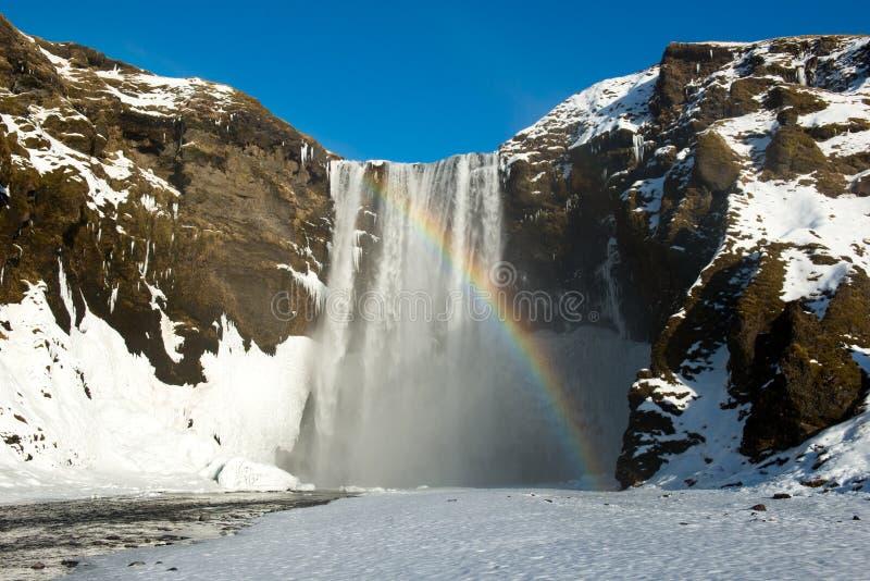 Водопад Skogafoss зимы с снегом и радугой, Исландией стоковые изображения