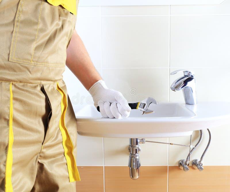 Водопроводчик в форме в ванной комнате стоковая фотография