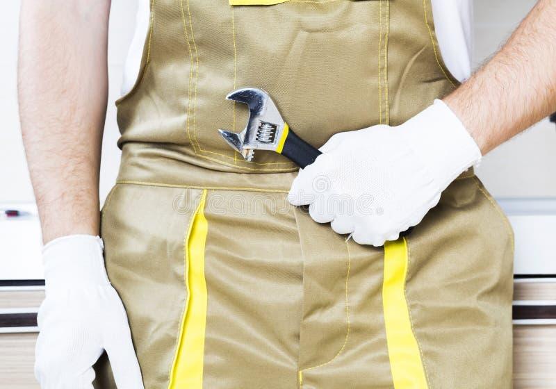Водопроводчик держа ключ стоковая фотография