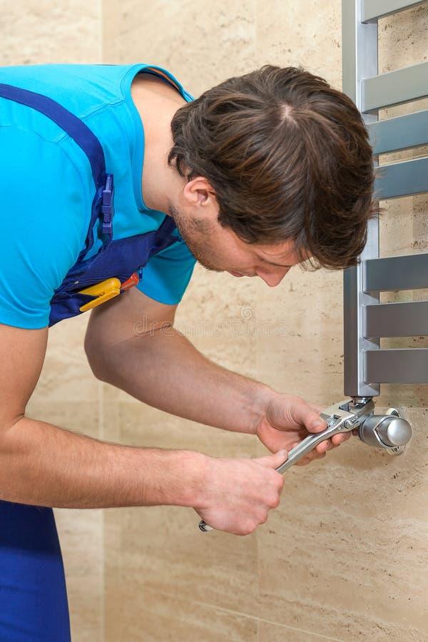Водопроводчик исправляя радиатор стоковые фото