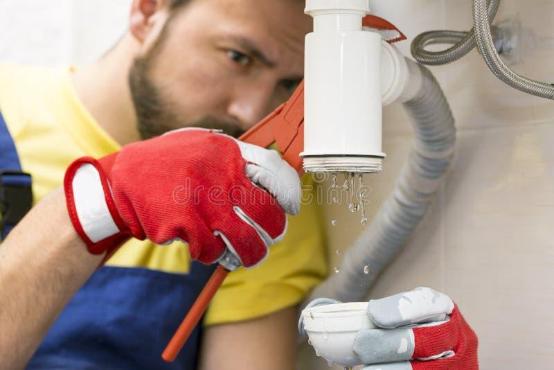 Водопроводчик исправляя сифон раковины в ванной комнате стоковое изображение rf