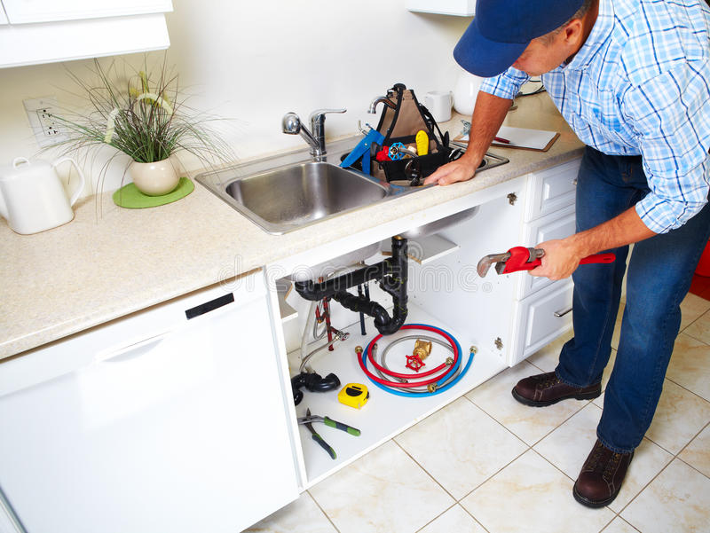 Водопроводчик на кухне стоковое фото rf
