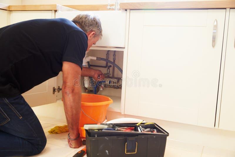 Водопроводчик постаретый серединой мужской исправляя кухонная раковина стоковое фото rf
