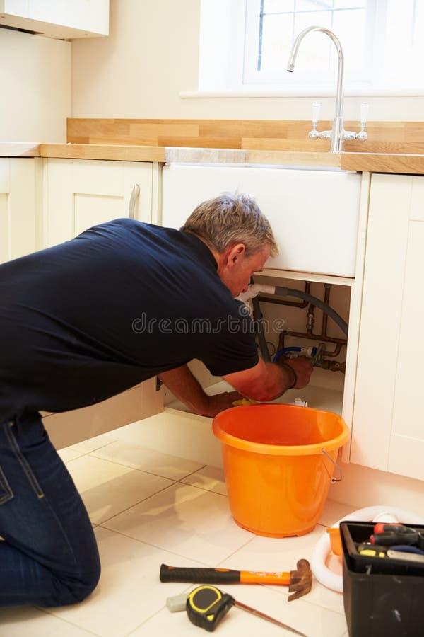Водопроводчик постаретый серединой мужской исправляя кухонная раковина стоковые фотографии rf