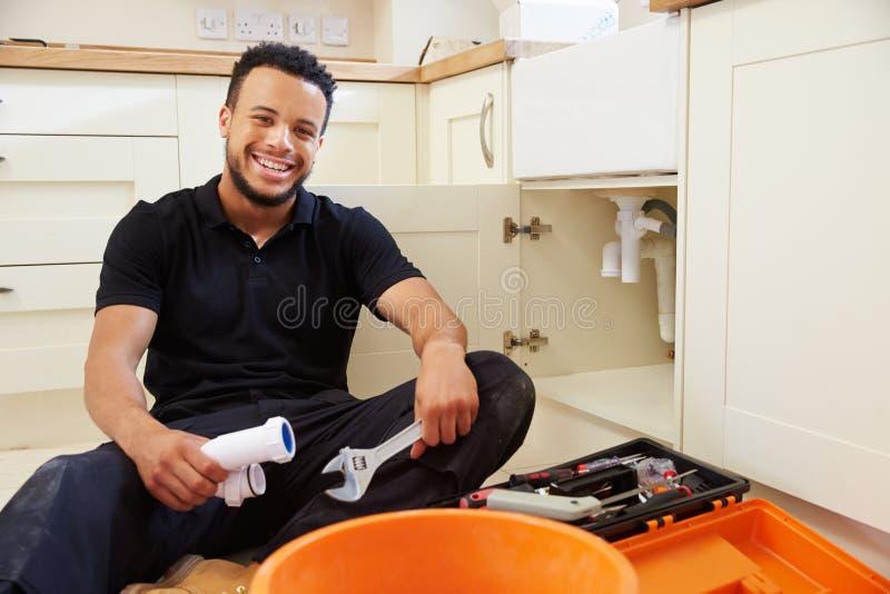 Водопроводчик сидя в кухне, портрет смешанной гонки стоковое фото
