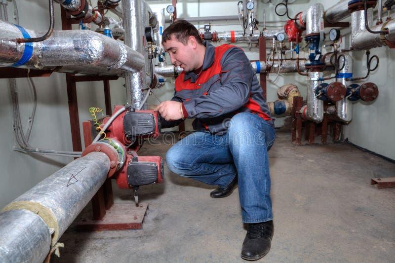 Водопроводчик устанавливая котельную системы отопления стоковое фото rf