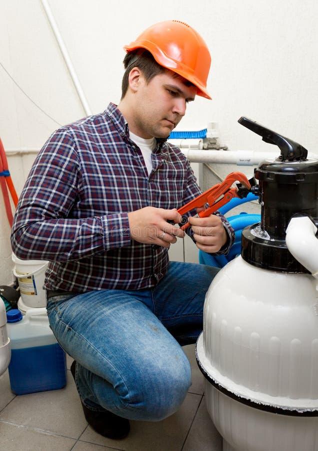 Водопроводчик устанавливая манометр на высокий бочонок давления стоковая фотография rf