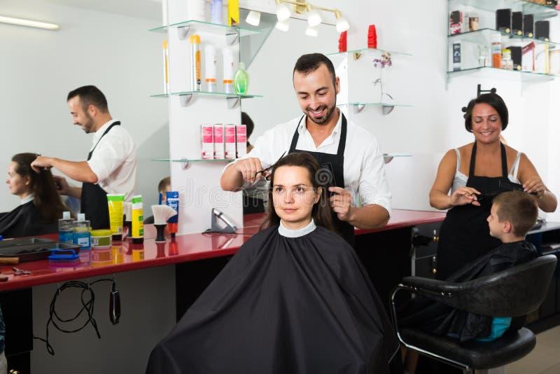 Волосы вырезывания парикмахера женского клиента стоковая фотография