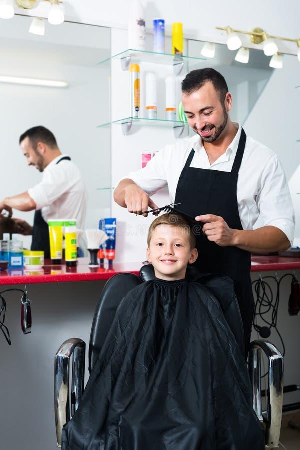 Волосы вырезывания парикмахера мальчика в салоне стоковые фотографии rf