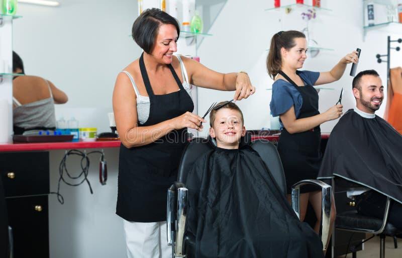 Волосы вырезывания парикмахера мальчика стоковая фотография rf