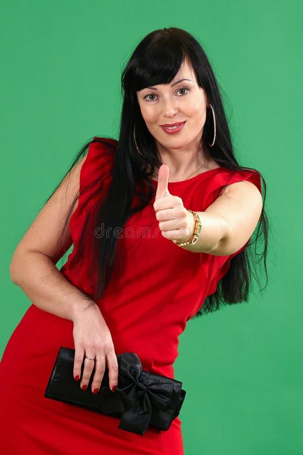 Волосы девушки черные в красном платье показывают О'КЕЫ на зеленом цвете стоковые фотографии rf