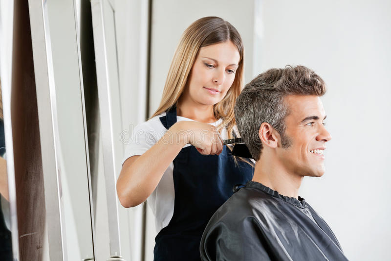 Волосы женского клиента вырезывания парикмахера стоковые изображения rf