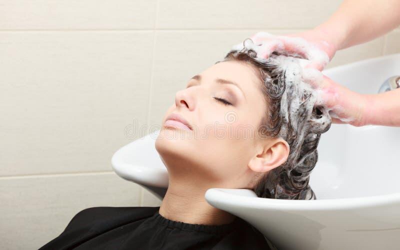 Волосы женщины парикмахера моя. Салон красоты парикмахерских услуг стоковые фотографии rf