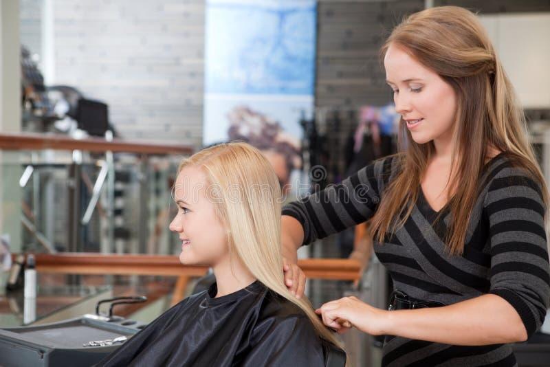 Волосы клиентов парикмахера чистя щеткой стоковое изображение
