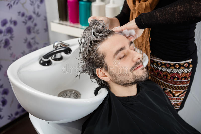 Волосы моя мужского клиента Beautician в салоне стоковая фотография