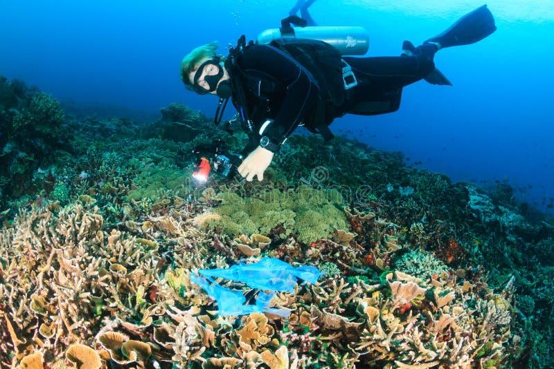 Водолаз плавая над сброшенным полиэтиленовым пакетом на рифе стоковые изображения