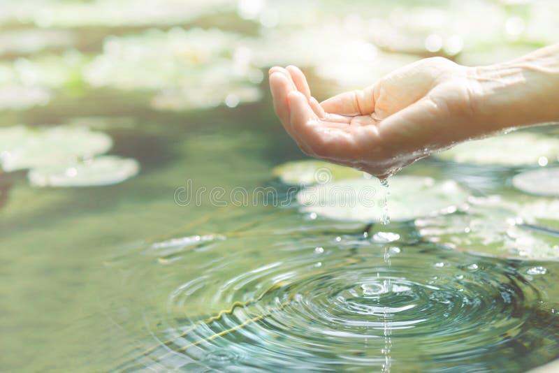 Волшебный контакт между человеческими рукой и водой стоковая фотография