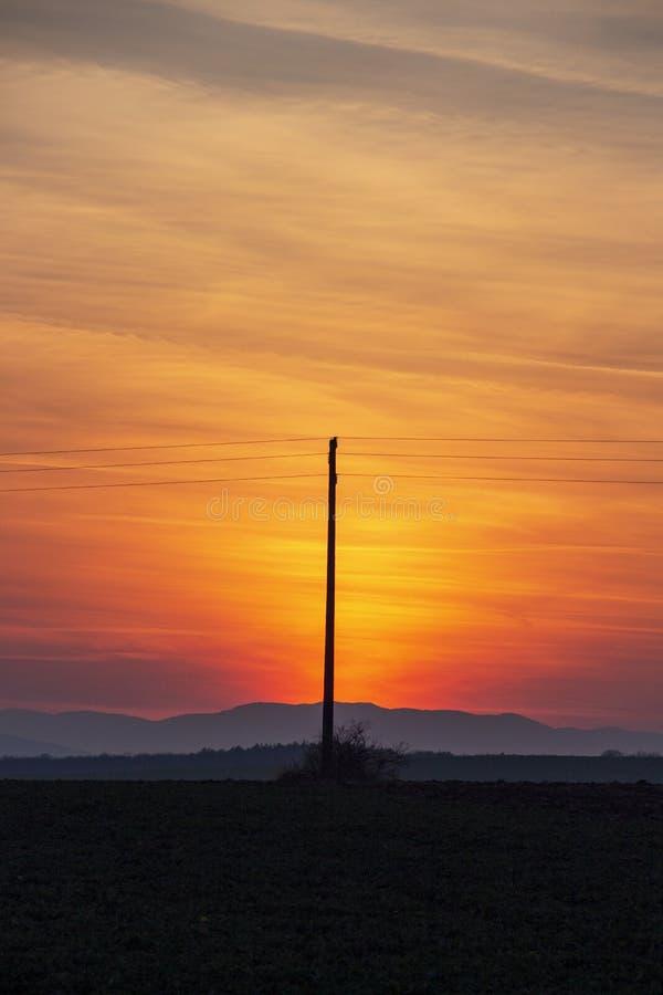 Впечатляющий заход солнца над вспаханным аграрным полем стоковая фотография rf