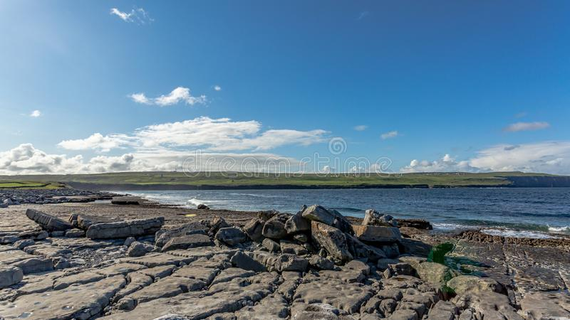 Впечатляющий обнаженный ландшафт и океан известняка в заливе Doolin со скалами Moher на заднем плане стоковая фотография