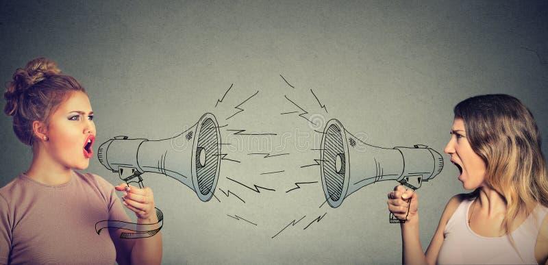 Враждуйте между 2 женщинами кричащими на одине другого в мегафоне стоковое фото rf