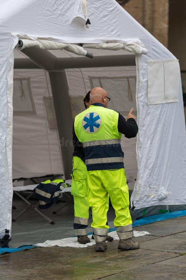 Врачи говоря вне белого временного шатра контрольного центра спасения стоковые фотографии rf