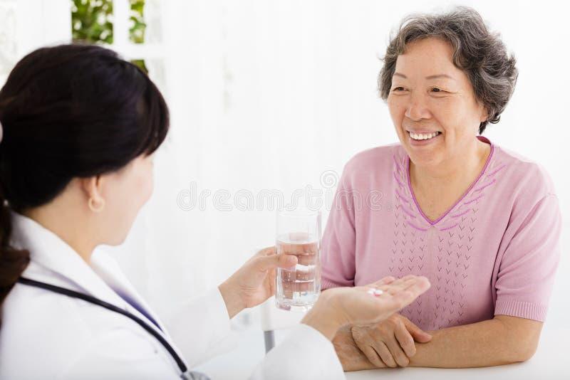 Врачуйте давать лекарство и воду к старшей женщине стоковое изображение rf